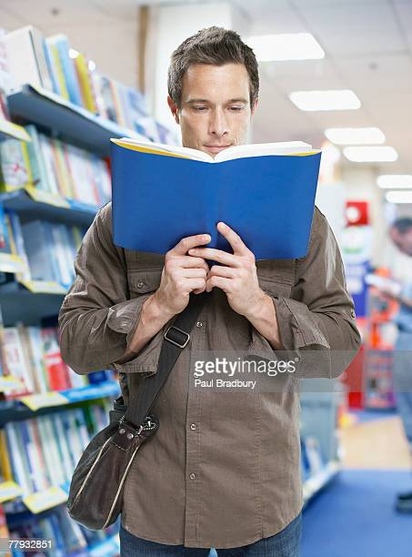 Man in store with book