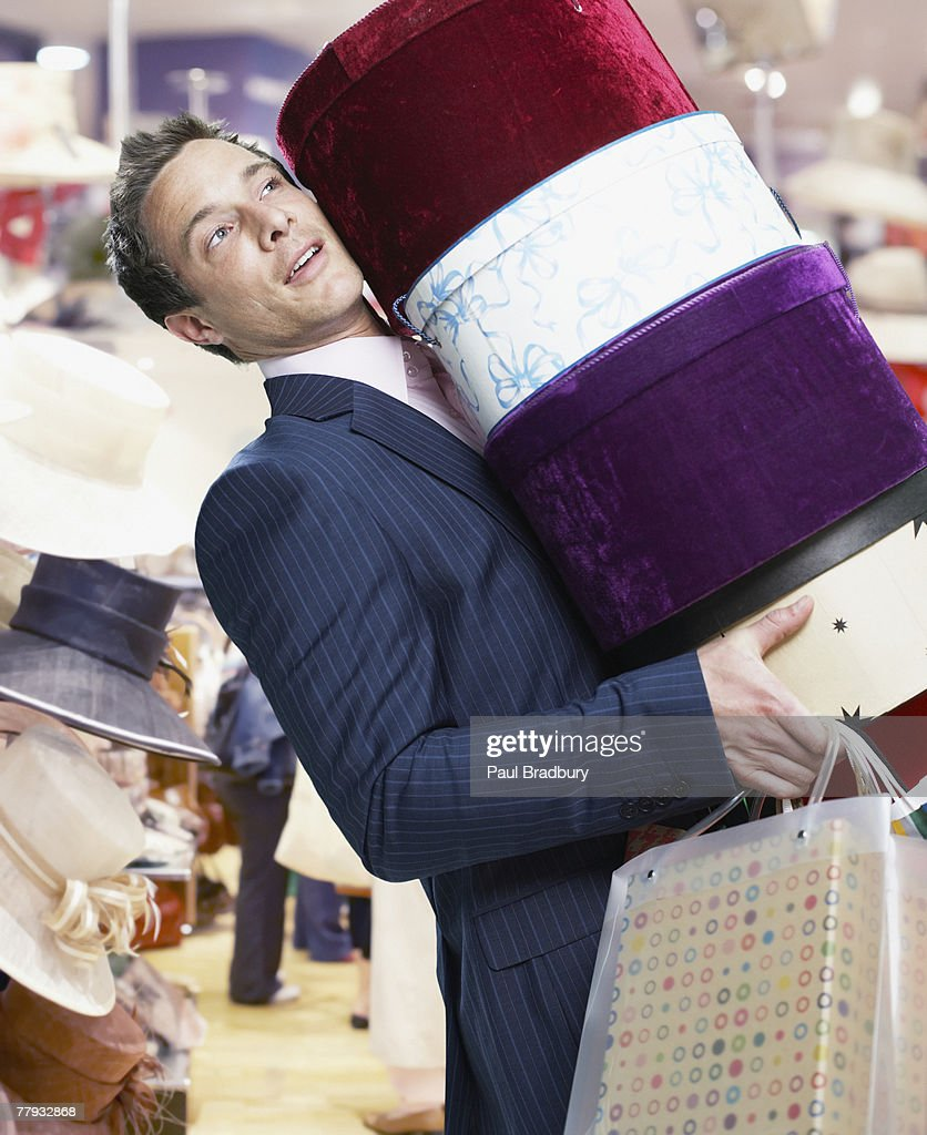 Man in store with hat boxes and shopping bags