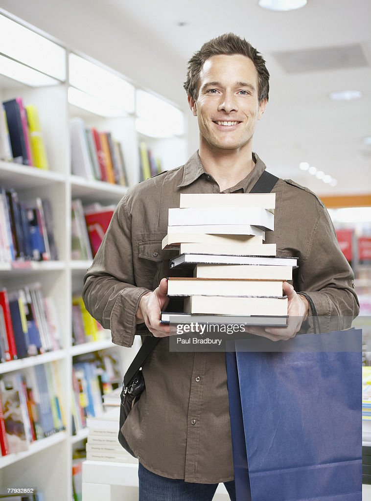 Man in store with stack of books : Stock Photo