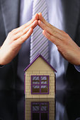 Man in suit and tie cover with arms little toy house closeup. Palm shelter save and trust defende owner wealth sell or rental structure loan idea no problems buy defence future plan concept