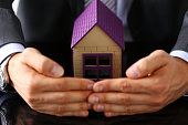 Man in suit and tie cover with arms little toy house closeup. Palm shelter, save and trust, defende owner wealth, sell or rental structure, loan idea, no problems, buy defence, future plan concept