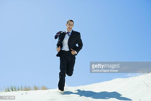 Man in suit and tie running across dune, laughing