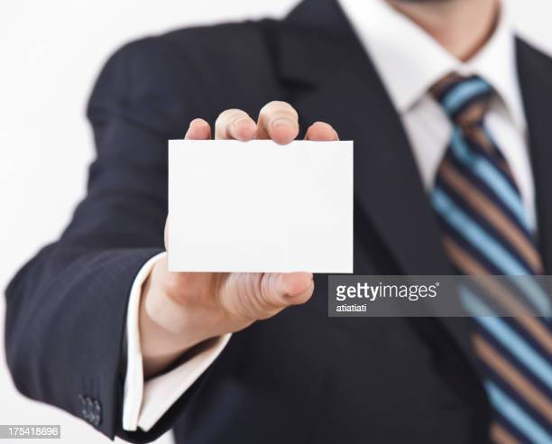 Man in suit arm outstretched holding blank business card