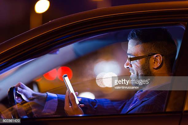 Man in suit at car by the night with phone
