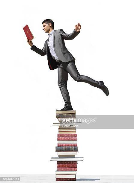 man in suit balancing on a lot of books reading .
