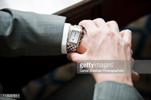 Man in suit checking watch : Stock Photo