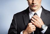 Man in suit fixing his tie.