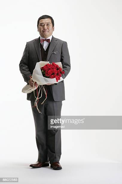 A man in suit holding a bouquet