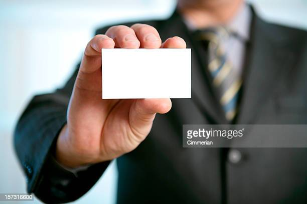 Man in suit holding blank business card in a his hand