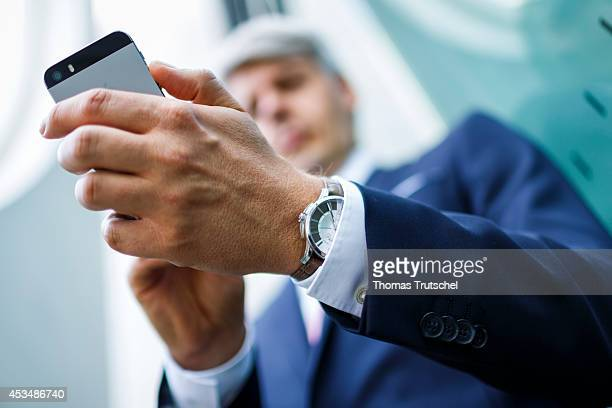 A man in suit holding his smartphone on August 07 2014 in Berlin Germany