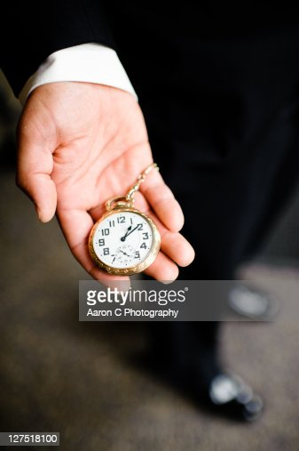 Man in suit holding old pocket watch on time