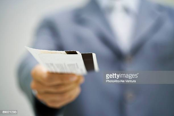 Man in suit holding out tickets