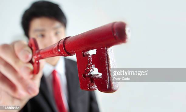 man in suit holding red key
