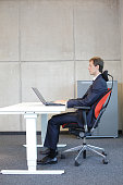 man in suit in correct sitting position at desk with laptop in office