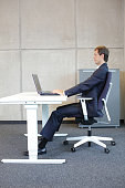 man in suit in correct sitting position at workstation