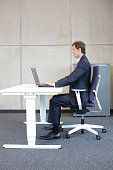 man in suit in correct sitting position at workstation in office