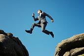 Man in suit jumping between towering rocks