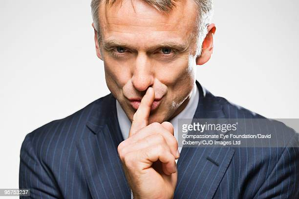 Man in suit making gesture to be quiet