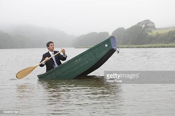 Man in suit paddling unbalanced boat