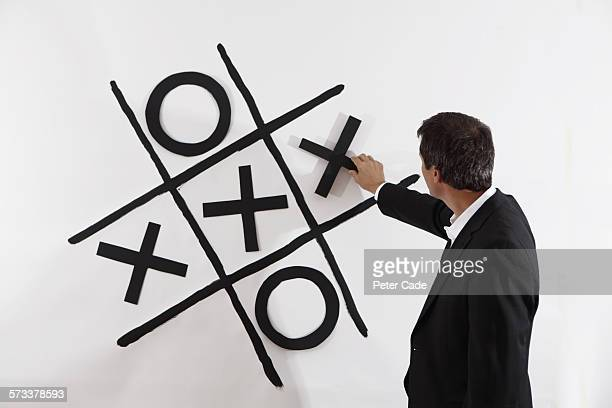 Man in suit playing giant noughts and crosses