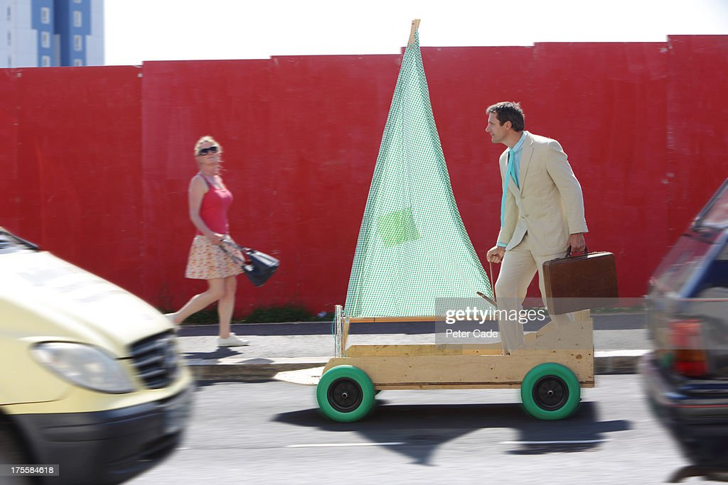 Man in suit riding kart with sail on road : Stock Photo