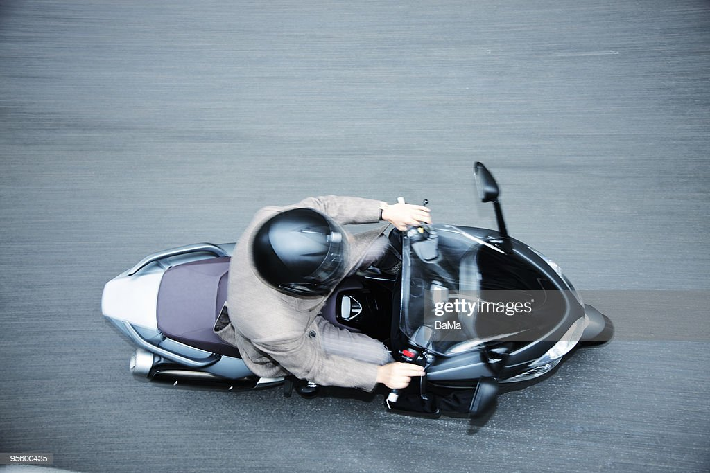 Man in suit riding moped