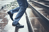 Man legs in suit running late up steps in rain