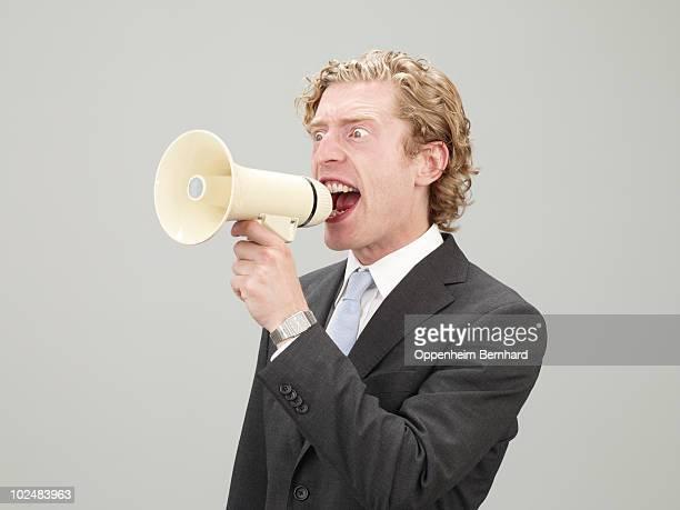 man in suit shouting through megaphone