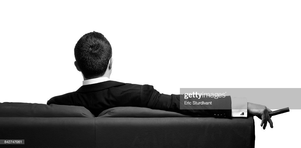 Man in suit sitting on couch with cigar