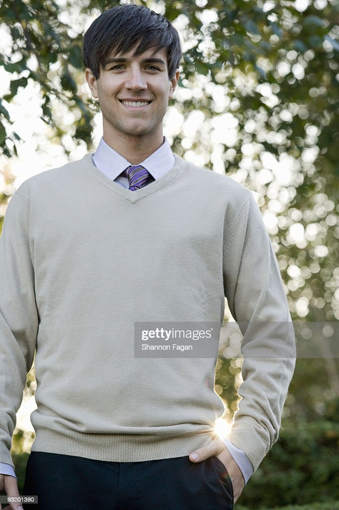 Man in suit smiling with hand in pocket at garden : Stock Photo