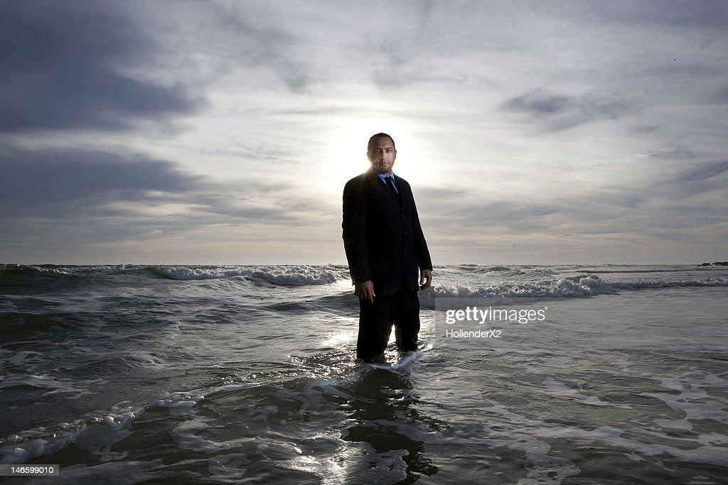 man in suit standing in ocean : Stock Photo