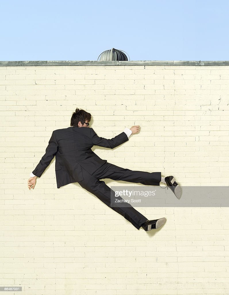 man in suit stuck to brick wall