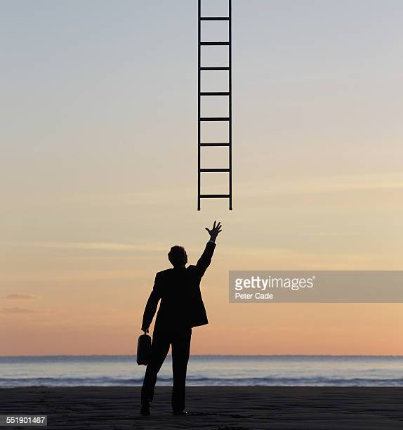 man in suit , sunset beach , reaching for ladder.