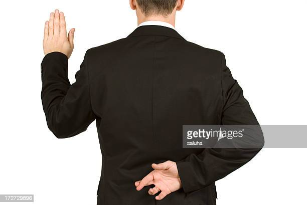 Man in suit taking oath while crossing fingers behind back