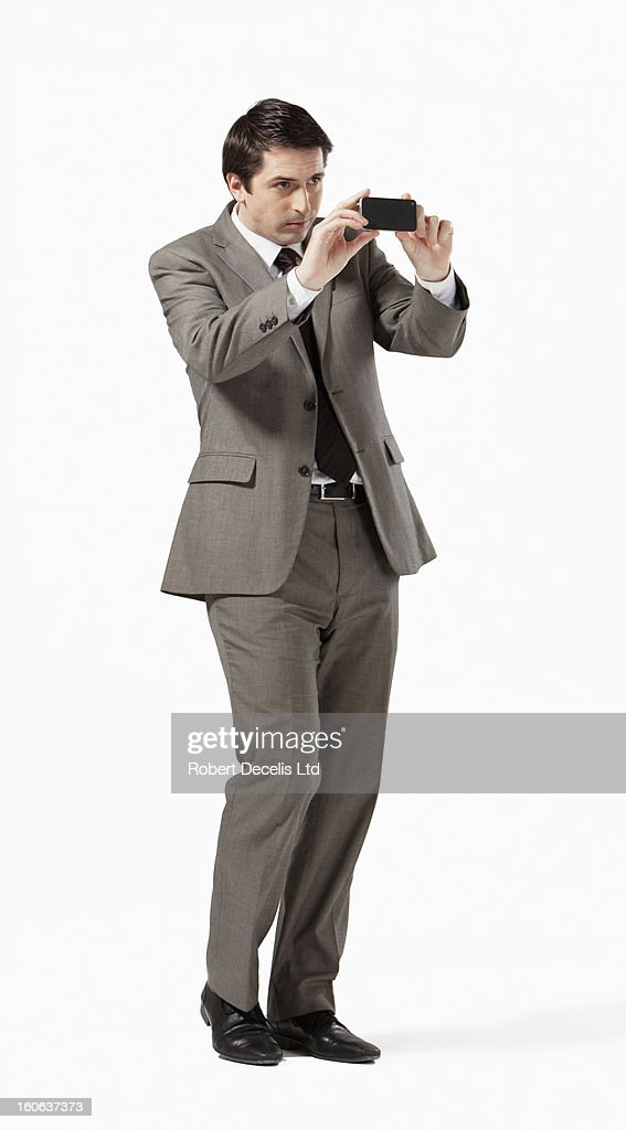 Man in suit using smart phone to take photograph