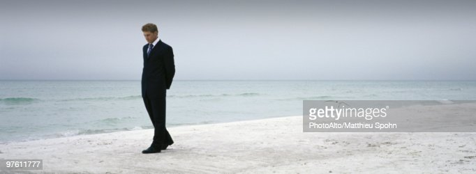 Man In Suit Walking On Beach Stock Photo Getty Images