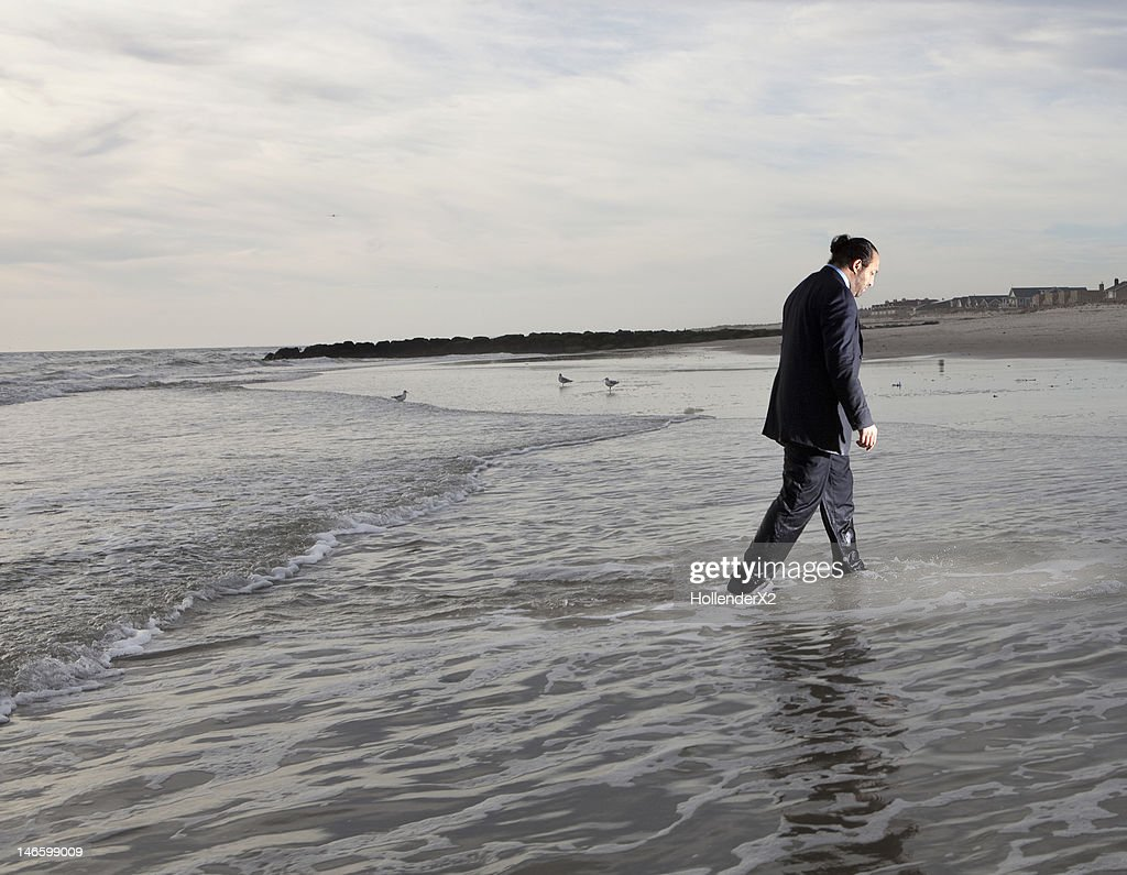 man in suit walking out of the ocean : Stock Photo