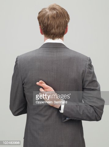 man in suit with fingers crossed behind back