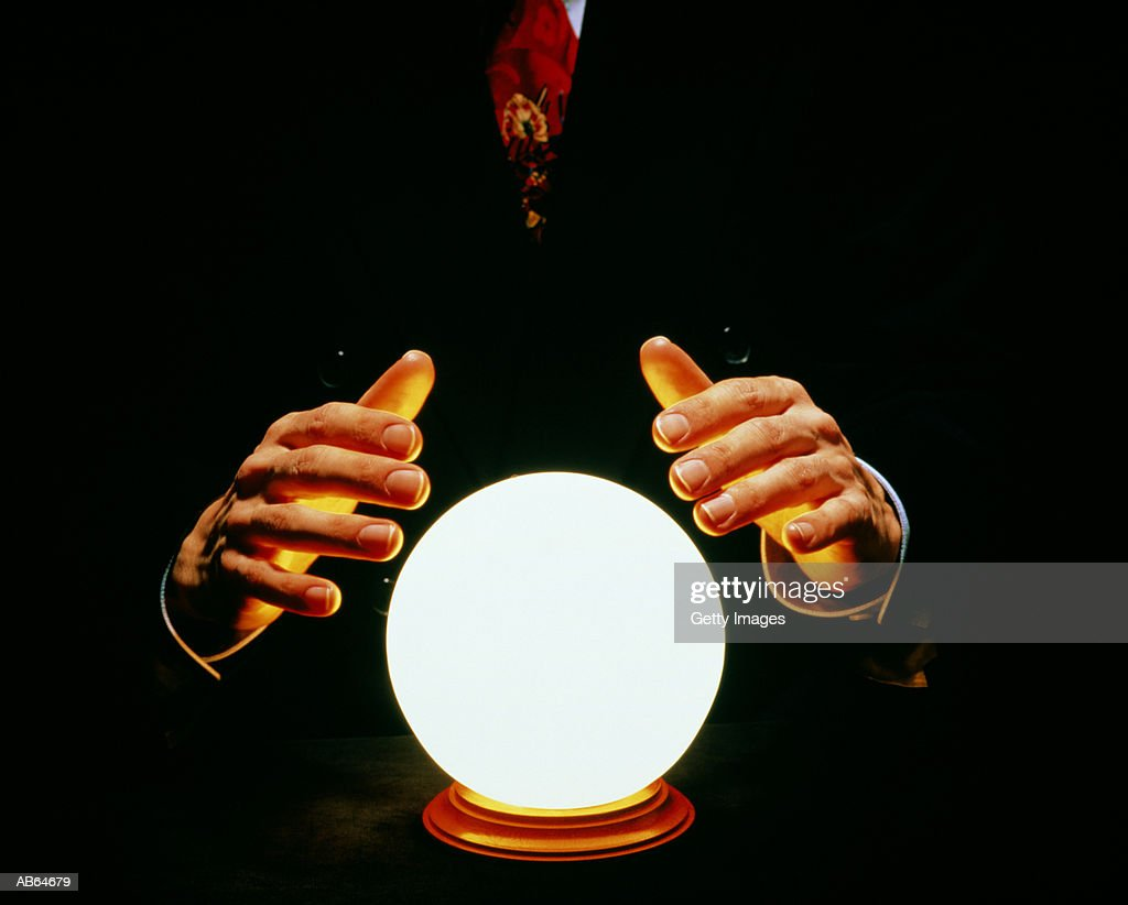 Man in suit with hands around glowing crystal ball : Stock Photo