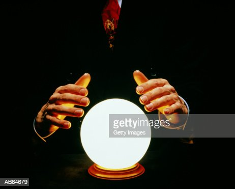 Man in suit with hands around glowing crystal ball : Foto de stock