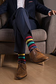 Man wearing a navy blue suit and brown leather shoes with funny colored socks