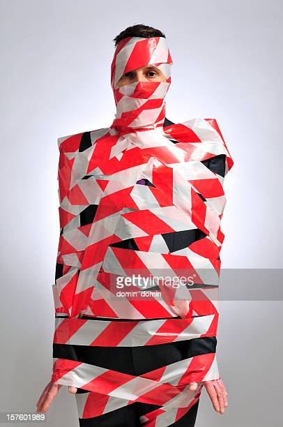 Man in suit wrapped in red and white warning tape