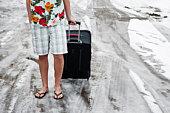 Man in summerwear with suitcase in snow