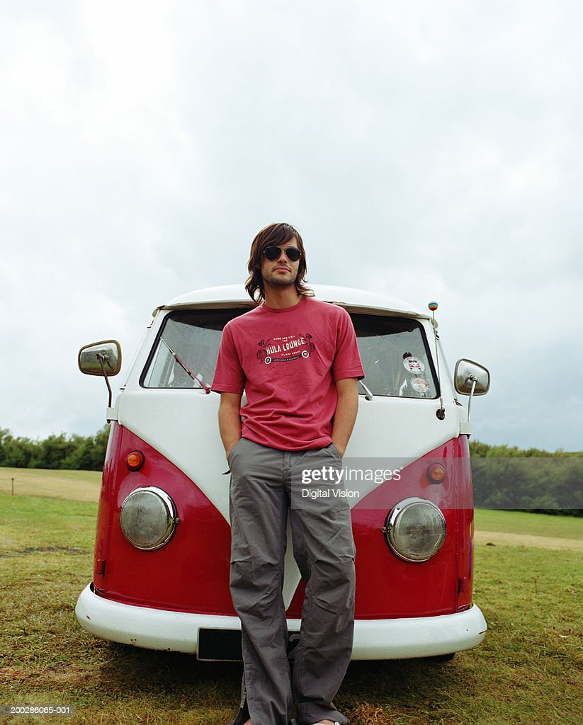Man in sunglasses standing in front of camper van, hands in pockets : Stock Photo