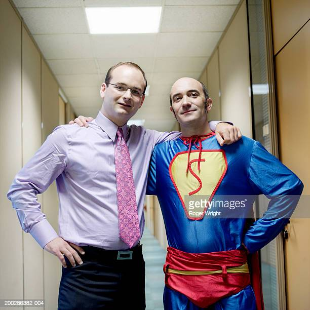 Man in superhero costume and businessman standing arm in arm, portrait