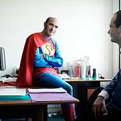 Man in superhero costume sitting on desk looking at businessman