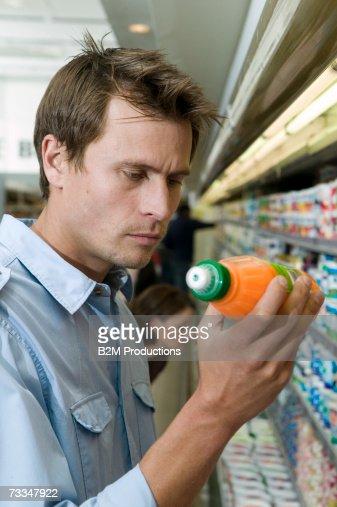 Man in supermarket, reading label on drinks bottle : Stock-Foto