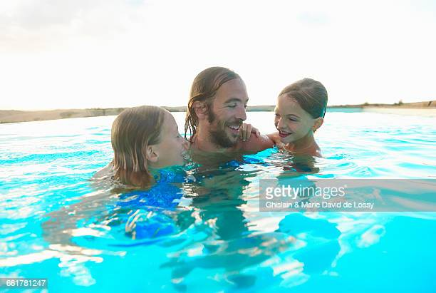 Man in swimming pool with daughter and son, Buonconvento, Tuscany, Italy