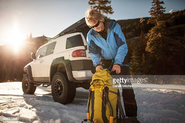 Man in the backcountry, packing his backpack.