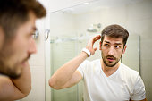Young man in the bathroom looking in the mirror and fixing his hair.